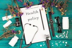 Stethoskop, Medizinklemmbrett mit Text u. x22; Gesundheit policy& x22; , Flasche, Gläser, Uhr und Pillen Stockfotografie