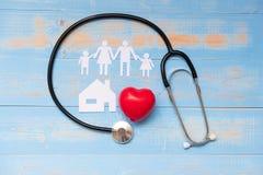 Stethoskop mit roter Herzform, Familien- und Hauspapier auf der blauen Pastellfarbe hölzern stockfotos