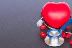 Stethoskop mit zwei roten Herzen und Pillen Stockfotografie