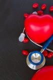 Stethoskop mit zwei roten Herzen und Pillen Stockbild