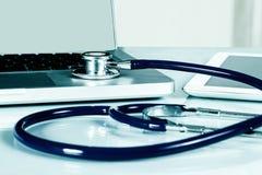 Stethoskop und Ausrüstung auf Schreibtisch lizenzfreies stockbild
