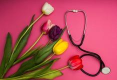 Stethoskop und bunte Tulpen auf einem rosa Hintergrund lizenzfreies stockfoto