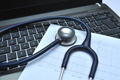 Stethoskop und Elektrokardiogramm auf einem Laptop Stockfotos