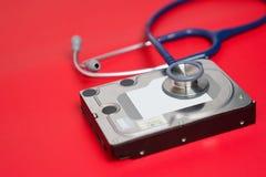 Stethoskop und Festplattenlaufwerk auf rotem Hintergrund Computerhardwarediagnose und Reparaturkonzept stockbild
