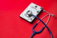 Stethoskop und Festplattenlaufwerk auf rotem Hintergrund Computerhardwarediagnose und Reparaturkonzept stockfotografie