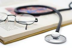 Stethoskop und Gläser auf einem Buch Stockfotografie