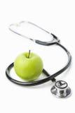 Stethoskop und grüner Apfel über Weiß Lizenzfreie Stockfotografie