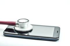 Stethoskop und intelligentes Telefon auf weißem Hintergrund Stockfotos