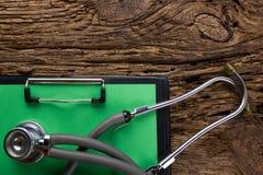 Stethoskop und Klemmbrett auf hölzerner Tischplatteansicht Medizinischer Hintergrund Konzept für Diät, Gesundheitswesen, Nahrung  Stockfoto