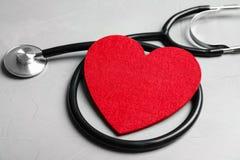 Stethoskop und rotes Herz auf grauem Hintergrund stockfoto