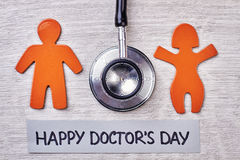 Stetoscope, stickmen on wooden surface. Happy Doctor`s Day Royalty Free Stock Photo
