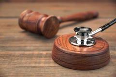 Stetoscope y mazo real de los jueces en el fondo de madera de Brown Imágenes de archivo libres de regalías