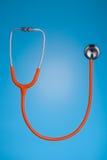 Stetoscopio arancio su fondo blu Immagini Stock Libere da Diritti