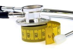 Stetoscopio che riposa su un metro molle della cucitrice fotografie stock libere da diritti