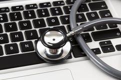 Stetoscopio che sta sulla tastiera di computer isolata su bianco immagini stock libere da diritti