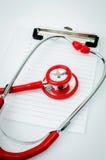 Stetoscopio con la lavagna per appunti di plastica, la carta in bianco e la penna Fotografia Stock