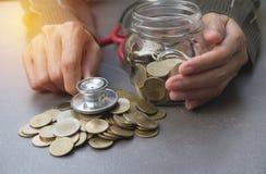Stetoscopio con le monete in barattolo con la pila dei soldi, finanza di concetto, Fotografie Stock