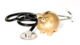 Stetoscopio della medicina con il salvadanaio dorato Fotografie Stock