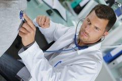 Stetoscopio della tenuta di medico a disposizione e facendo auscultazione fotografie stock