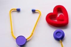 Stetoscopio e cuore medici su un fondo bianco fotografie stock