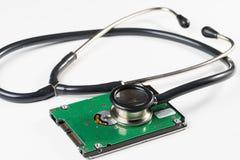 Stetoscopio e drive del hard disk su fondo bianco Immagine Stock