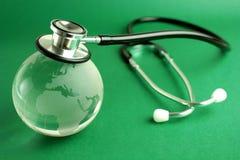 Stetoscopio e globo del cristallo su priorità bassa verde Immagini Stock Libere da Diritti