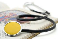 Stetoscopio giallo su un libro Immagine Stock Libera da Diritti