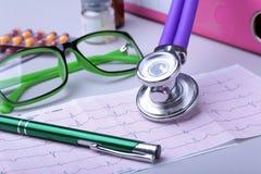 Stetoscopio medico che si trova sul grafico del cardiogramma con il mucchio del primo piano delle pillole Cura di cardiologia, sa fotografia stock libera da diritti