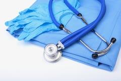 Stetoscopio medico e guanti che si trovano sulla fine di medico dell'uniforme del blu su Il deposito degli strumenti medici e deg Fotografie Stock Libere da Diritti