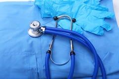 Stetoscopio medico e guanti che si trovano sulla fine di medico dell'uniforme del blu su Il deposito degli strumenti medici e deg Fotografie Stock