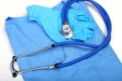 Stetoscopio medico e guanti che si trovano sulla fine di medico dell'uniforme del blu su Il deposito degli strumenti medici e deg Immagini Stock Libere da Diritti