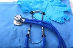 Stetoscopio medico e guanti che si trovano sulla fine di medico dell'uniforme del blu su Il deposito degli strumenti medici e deg Fotografia Stock Libera da Diritti