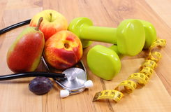 Stetoscopio medico, frutti e teste di legno per utilizzare nella forma fisica Fotografie Stock Libere da Diritti