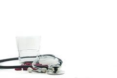 Stetoscopio, pillole e bicchiere d'acqua con fondo bianco Fotografia Stock
