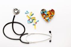 Stetoscopio su fondo bianco con le pillole nella forma di cuore Fotografie Stock Libere da Diritti
