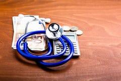Stetoscopio su un calcolatore e sui soldi Fotografia Stock Libera da Diritti