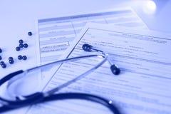 Stetoscopio sulla tavola fra le pillole e la forma medica di r fotografia stock libera da diritti