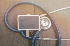 Stetoskop över träbakgrund för läkarundersökning och hälsovård royaltyfri fotografi