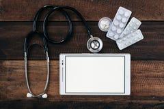 Stetoskop, cyfrowa pastylka i medycyna na drewnianym stołowym tle, zdjęcia royalty free