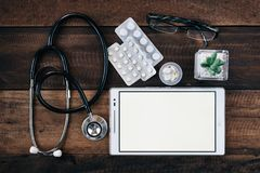 Stetoskop, cyfrowa pastylka i medycyna na drewnianym stołowym tle, zdjęcia stock