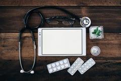 Stetoskop, cyfrowa pastylka i medycyna na drewnianym stołowym tle, zdjęcie stock