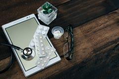 Stetoskop, cyfrowa pastylka i medycyna na drewnianym stołowym tle, obrazy stock