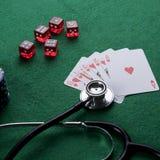 Stetoskop, czerwoni sze?ciany i grzebak karty do gry jako uprawia? hazard z tw?j zdrowia poj?ciem, obraz stock