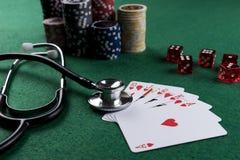 Stetoskop, czerwoni sze?ciany i grzebak karty do gry jako uprawia? hazard z tw?j zdrowia poj?ciem, obrazy royalty free