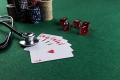 Stetoskop, czerwoni sze?ciany i grzebak karty do gry jako uprawia? hazard z tw?j zdrowia poj?ciem, zdjęcia royalty free