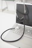 Stetoskop drapujący nad srebnym laptopem Zdjęcie Royalty Free