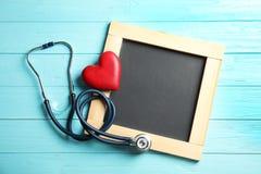 Stetoskop, hjärta och svart tavla med utrymme för text på träbakgrund, bästa sikt cardiology arkivfoto