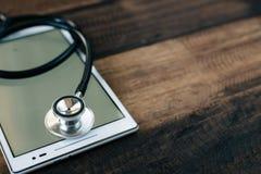 Stetoskop i cyfrowa pastylka na drewnianym stołowym tle fotografia royalty free