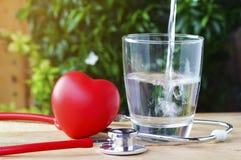 Stetoskop i czerwieni serce z wodą na drewnianym tle Fotografia Royalty Free