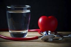 Stetoskop i czerwieni serce z wodą na drewnie Obraz Royalty Free
